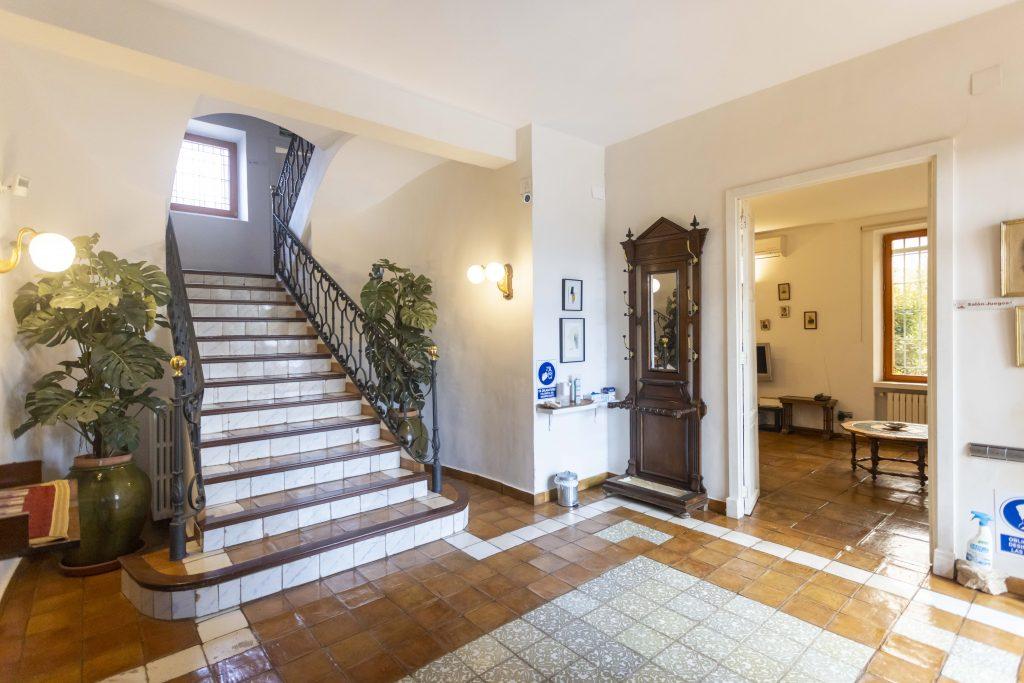 Entrada señorial de La Nova Alcudia. Recepción amplia con escaleras y plantas. Bien iluminada y desinfectada.