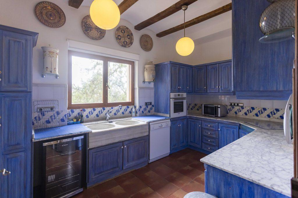 Gran cocina azul de La Nova Alcudia. Equipada con horno, microondas, vitrocerámica, cubiertos, peso para alimentos, lavadero, vinoteca, nevera y congelador, entre otros.