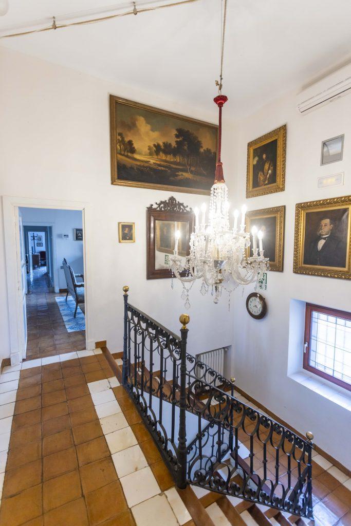 Escalera central de La Nova Alcudia, lena de cuadros originales de la época y una gran lámpara señorial de cristal.